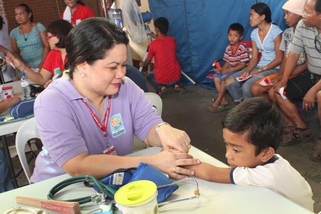 A DZMM TLC volunteer attends to a child